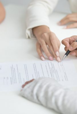 Close up of wife hands signing divorce decree after break up decision, female lawyer showing where to sign papers. Concept of unsuccessful marriage, couple finishing relationship, legal separation